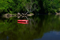 A lone kayak sits in a a calm cove Stock Photos
