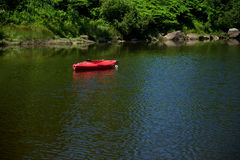 A lone kayak sits in a a calm cove Royalty Free Stock Photo