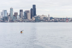 A lone kayaker paddles toward the Seattle skyline. A lone kayaker paddles toward the Seattle skyline on a calm spring day Stock Images