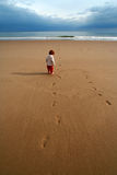 Lone kid on the beach. A wide angle shot of a seemingly lost young boy on a vast empty beach royalty free stock photo