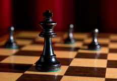 Lone king on chess board. Chess board with king alone as example of game or business concept for power; strategy or success stock photos