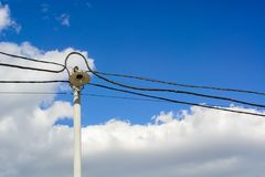 A lone lantern and wires to it on a high pole. A blue spring sky and clouds. Royalty Free Stock Photos