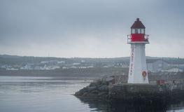 A lone lighthouse atop an outcropping of rock in the Bay of Grand Bank, Newfoundland, on a gray sky, summer morning. Red & white lighthouse in quiet Grand Bank stock photo