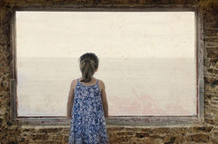 Lone little girl looking the sea. Lone little girl standing on window in front of the sea Stock Image