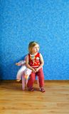 Lone little girl sitting on a chair with a doll Stock Image
