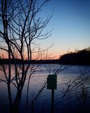 Lone mailbox near serene lake during sunset. Mailbox near frosty lake during sunset in seekonk Massachusetts Royalty Free Stock Images