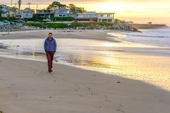 Lone man on beach at sunrise Stock Photos