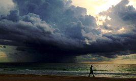 Lone man followed by a huge cloud Royalty Free Stock Images