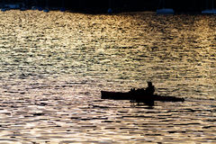 Lone man in kayak as silhouette at. Sunset against red colored water, concept for relaxing, meditating, thinking, being in balance, enjoying silence escape from Royalty Free Stock Photo