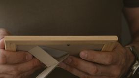 A lonely man standing at the window holding a photo in a wooden frame. The man examines the photo. A lone man in a khaki t-shirt standing at the window holding stock video