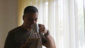 Alone man in a khaki t-shirt standing at the window holding a photo in a wooden frame. The man exams the photo and. A lone man in a khaki t-shirt stood by the stock video footage
