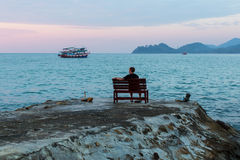 Lone man sitting on a bench at the evening sea coast. Travel. Stock Photo