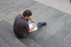 Lone man sitting on exterior steps reading a book Royalty Free Stock Photo