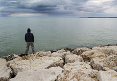 Lone man stand in front of the sea. On a bad weather day Royalty Free Stock Photos