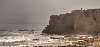 Free Lone Man Stands At A Vista As Fog Drifts In Over The Ocean At Cr Stock Photography - 101073462