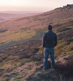 Lone man stares out over grassland during sunset royalty free stock photo