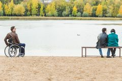 A lone man in a wheelchair and a couple on a park bench. royalty free stock images