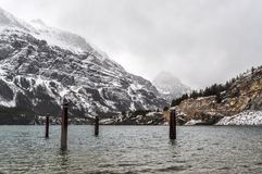 Lone Mooring Post Stand in Icy Lake Glacier National Park stock photo