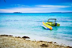 Lone motorboat with banana boat on the sea water stock photo