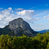 A lone Mountain, forest and blue cleare sky Royalty Free Stock Photo