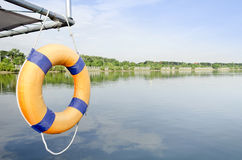 Lone orange life ring  in front of empty boat docks on a cloudy Stock Image