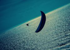 A lone paraglider over a silver sea with dark clouds at dusk Royalty Free Stock Photo