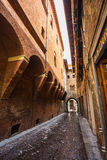 A lone passerby with an umbrella on a narrow street in the old c. Ity of Bologna Italy Royalty Free Stock Photos