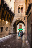 A lone passerby with an umbrella on a narrow street in the old c. Ity of Bologna Italy Stock Photo