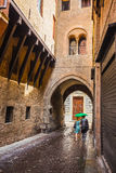 A lone passerby with an umbrella on a narrow street in the old c. Ity of Bologna Italy Royalty Free Stock Photography