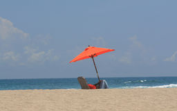 Lone person on beach under umbrella Stock Photos