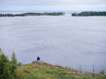 Lone person looking at lake. Lone person figure sitting on shore of huge Ladoga lake in Karelia, northern Russia Royalty Free Stock Images