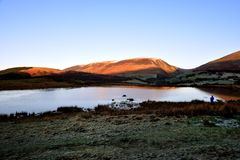 Sunrise on Skiddaw and Latrigg. Lone Photographer at Tewet Tarn Stock Photography
