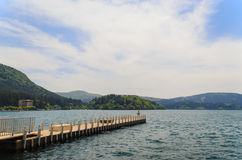 Lone pier on a beautiful lake with greenish water surrounded Royalty Free Stock Image