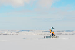 Lone Pumpjack in Snowy Field. Landscape of a lone orange pumpjack in a snow covered field Stock Photography