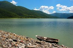 Lone punt boat on rocky lake shore.  Stock Photography