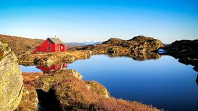 A Lone Red Cabin on The Top of Mountain. Image of a red cabin by a pond on the top of Mount Ulriken in Bergen, Hordaland County, Norway royalty free stock photo