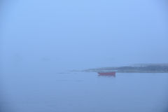 A lone red rowboat or skiff in heavy fog. A lone red rowboat or skiff sits moored on a calm and foggy morning off the Maine Coast Royalty Free Stock Images