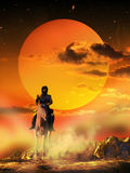 Lone rider. Man riding lonely under the sunset, on an arid land Royalty Free Stock Photography