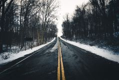 Lone road going off into distance during winter royalty free stock photos