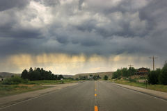 Lone road with threatning dark rain clouds stock images