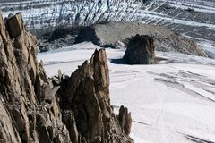 Lone rock climber on top of pinnacle overlooking glacier Royalty Free Stock Photo