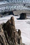 Lone rock climber on top of pinnacle overlooking glacier Stock Photo