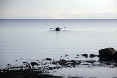 Lone rowing boat on evening sea with horizon, blue water and sky stock image
