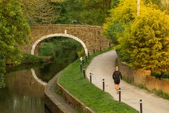 Jogging as the sun sets. A lone runner exercises along the tow path of the Leeds and Liverpool Canal at Dowley Gap near Hirst Wood, Shipley, Yorkshire caught in stock photo