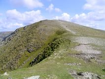Lone runner heading up Dollywagon Pike, looking from High Crag Royalty Free Stock Image