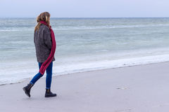 Lone sad beautiful girl walking along the shore of the frozen sea on a cold day, rubella, chicken with a red scarf on the neck Royalty Free Stock Image