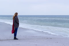 Free Lone Sad Beautiful Girl Walking Along The Shore Of The Frozen Sea On A Cold Day, Rubella, Chicken With A Red Scarf On The Neck Royalty Free Stock Photo - 65095215