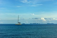 A lone sail boat in the blue sea Stock Photos