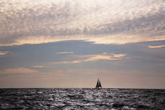 Lone sailboat on horizon. Ocean with a lone sailboat stock images