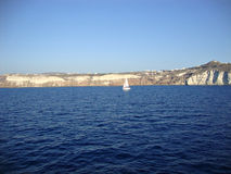 A lone sailboat off the coast of the Greek island of Santorini Royalty Free Stock Photography